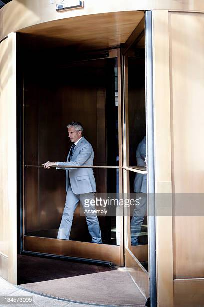 Businessman walking out of a revolving door.