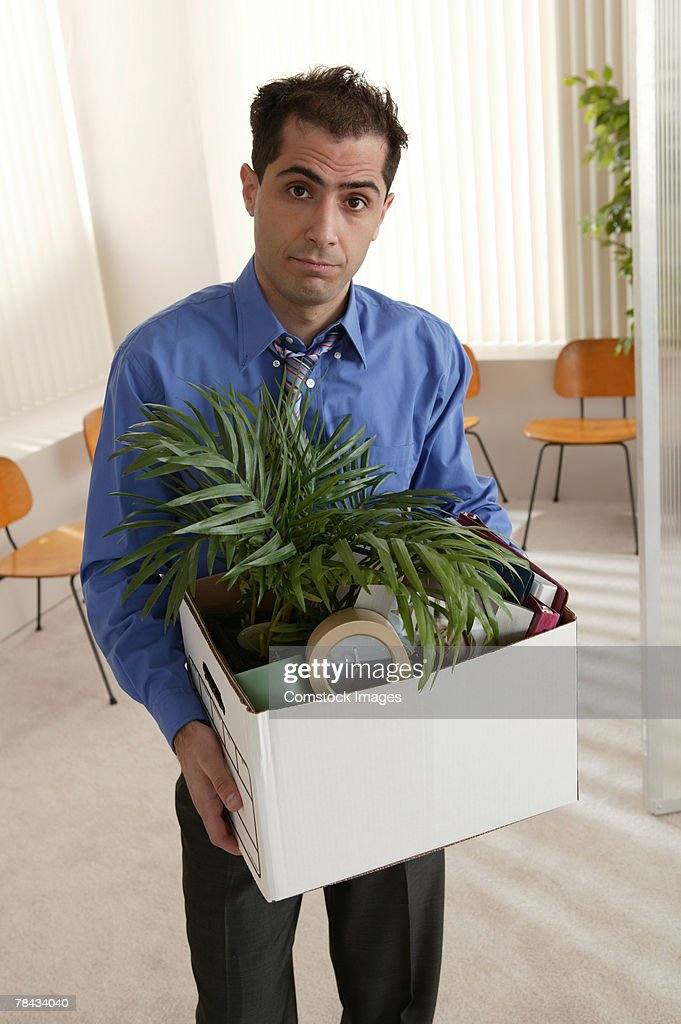 Businessman walking out of office with box full of stuff : Stockfoto