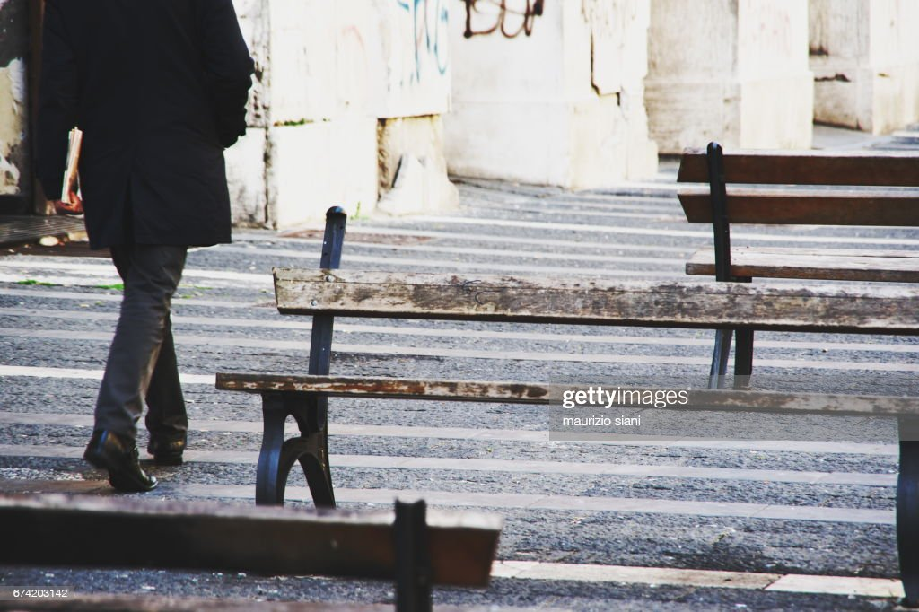 Businessman walking outdoors between benches : Stock Photo