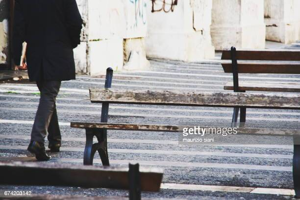 businessman walking outdoors between benches - persona in secondo piano stock pictures, royalty-free photos & images