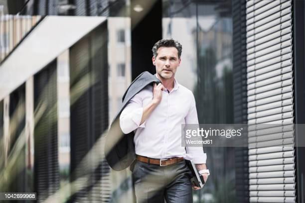 businessman walking outside office building - chaqueta fotografías e imágenes de stock