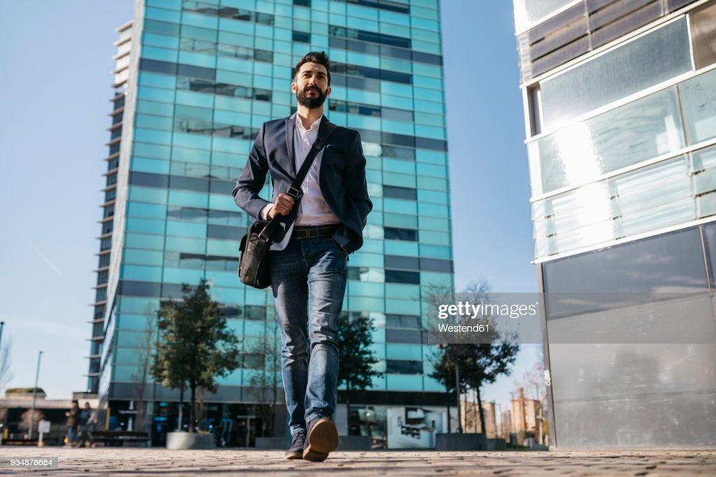 Businessman walking outside office building : ストックフォト