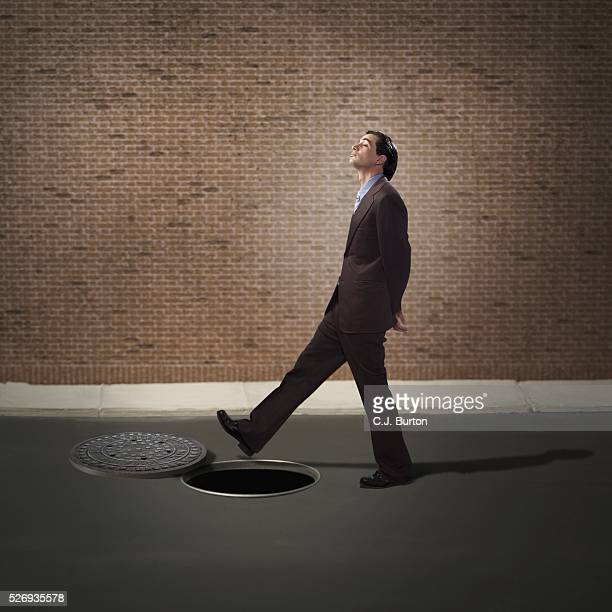businessman walking over manhole - bad luck stock pictures, royalty-free photos & images