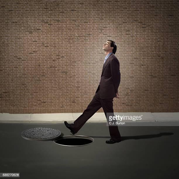 Businessman walking over open manhole