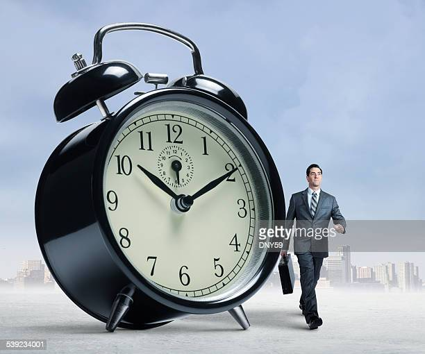 Businessman walking past a large alarm clock