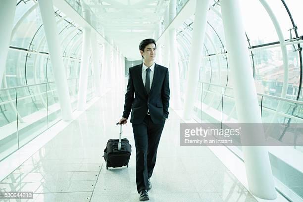 Businessman walking through a glass tunnel