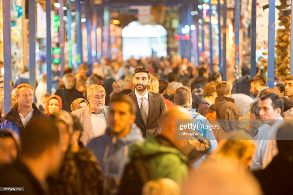 Businessman walking through bazaar : Stock Photo