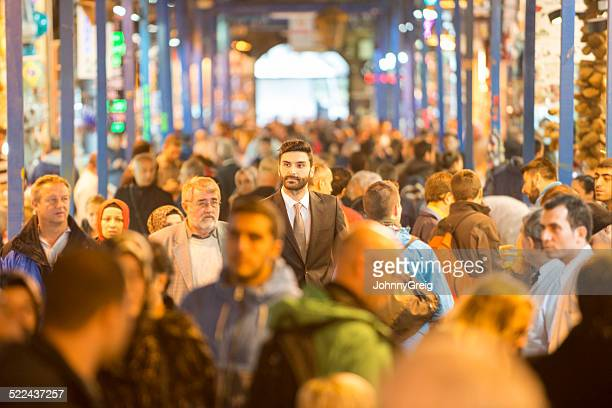 businessman walking through bazaar - bazaar stockfoto's en -beelden