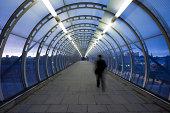 Businessman Walking Through Glass Skywalk at Twilight