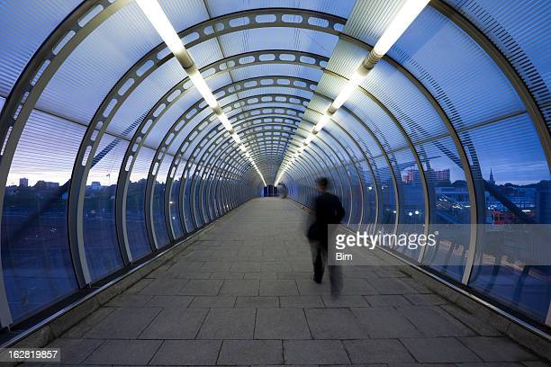Businessman Walking Through Glass Skywalk at Twilight