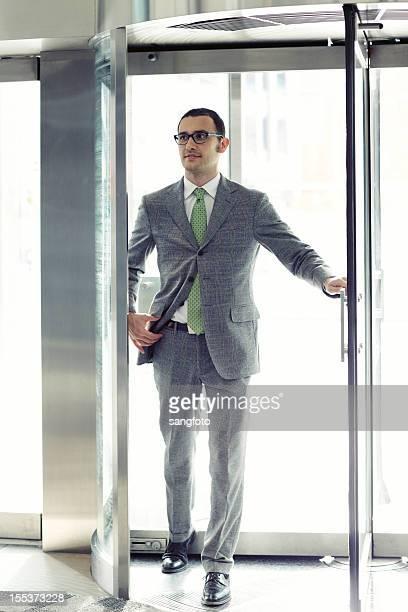 Businessman walking through revolving door