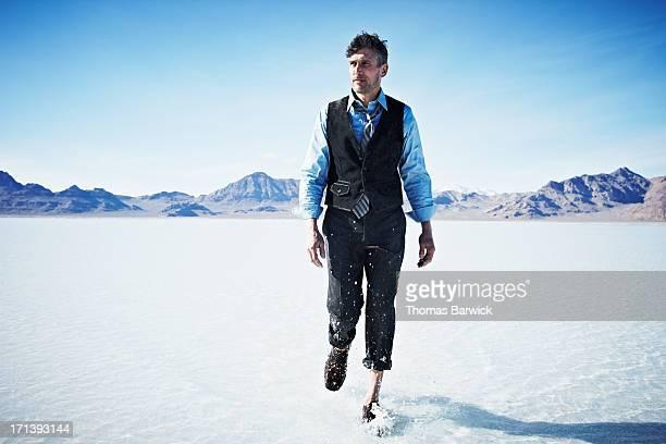 Businessman walking through shallow water