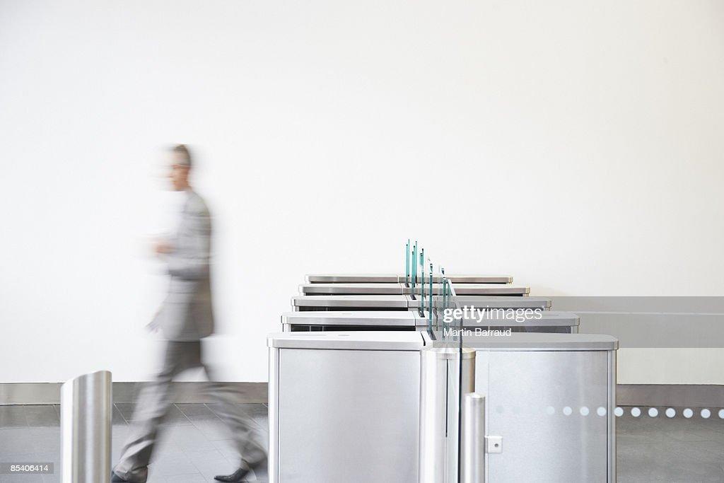 Businessman walking through turnstile : Stock Photo
