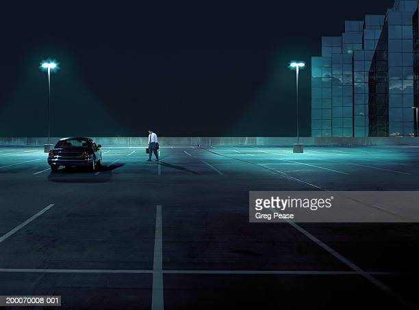 businessman walking toward car in empty parking lot at night - empty lot night stock pictures, royalty-free photos & images