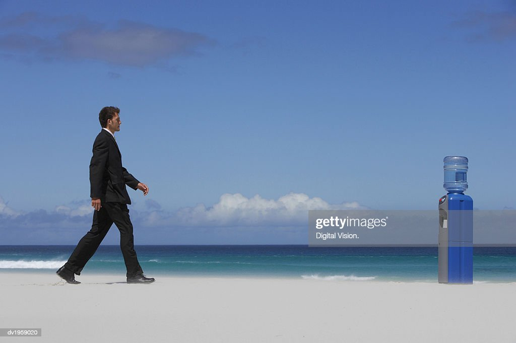 Businessman Walking Towards a Water Cooler on a Beach : Stock Photo