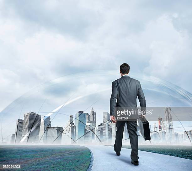 Businessman walking towards protected futuristic city