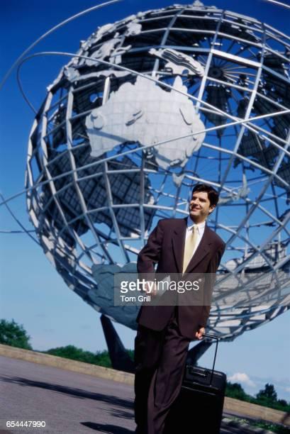 Businessman Walking Underneath Globe