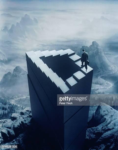 Businessman walking up infinite staircase, landscape background