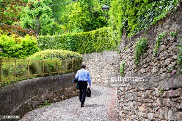 businessman walking up old pathway in bergamo - bergamo stock pictures, royalty-free photos & images