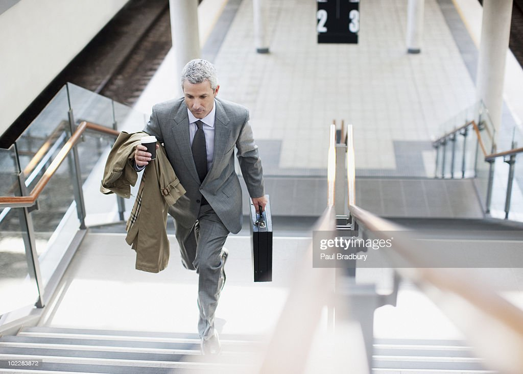 Businessman walking up stairs in train station : Stock Photo