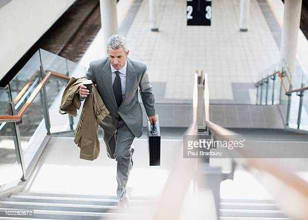businessman walking up stairs in train station - railroad station stock pictures, royalty-free photos & images