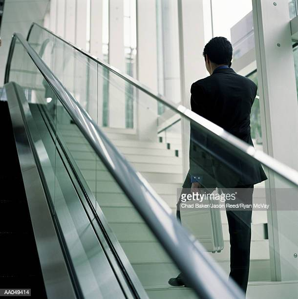 Businessman walking up stairs, talking on cell phone, low angle view