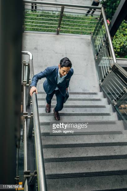 businessman walking up the steps downtown in taipei - south_agency stock pictures, royalty-free photos & images
