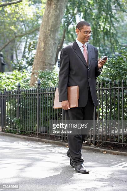 Businessman walking using PDA, smiling