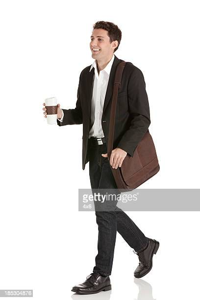 Businessman walking with a disposable cup