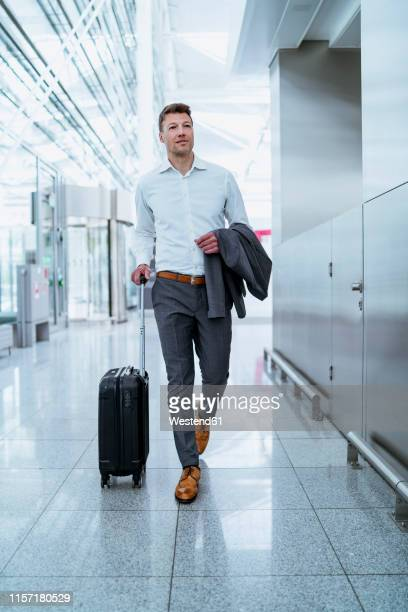 businessman walking with baggage at the airport - wheeled luggage stock photos and pictures