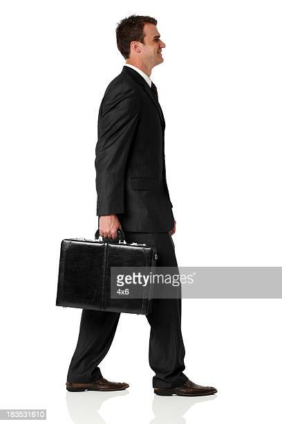 businessman walking with briefcase and smiling - briefcase stock photos and pictures