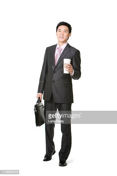 Businessman walking with coffee cup and brief case in hand