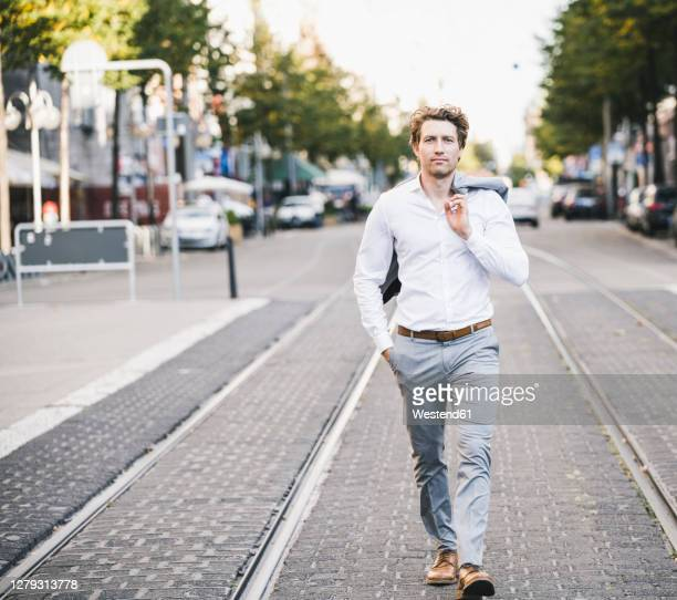 businessman walking with hand in pocket and jacket over shoulder in city - businesswear stock pictures, royalty-free photos & images