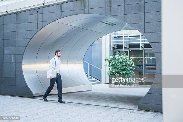 Businessman walking with laptop, Munich, Bavaria, Germany