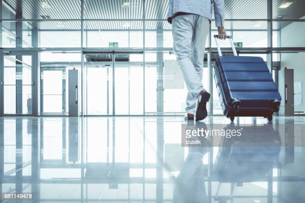 Businessman walking with luggage in airport