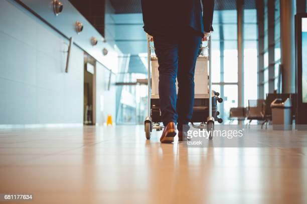 Homme d'affaires à pied avec bagages au terminal de l'aéroport