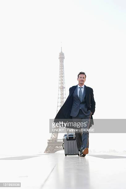Businessman walking with luggage with the Eiffel Tower in the background, Paris, Ile-de-France, France