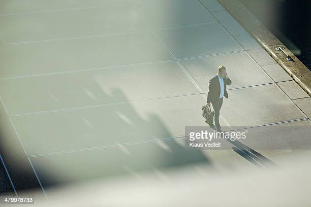 Businessman walking with phone in low light