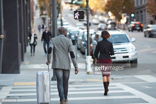 Businessman walking with rolling suitcase in pedestrian crossing