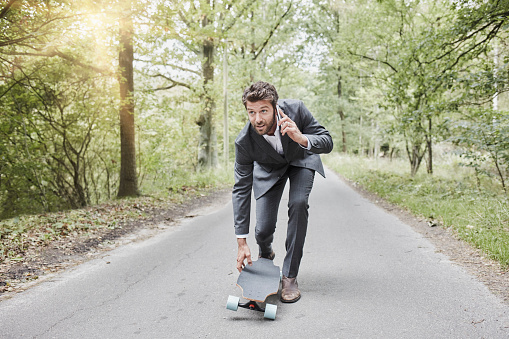Businessman walking with skateboard and smartphone on rural road - gettyimageskorea