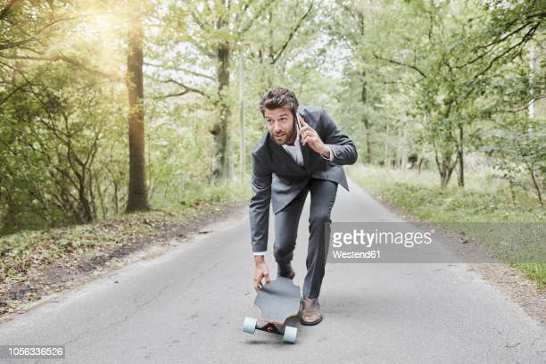 Businessman walking with skateboard and smartphone on rural road