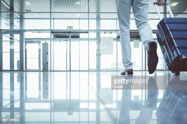 Homme d'affaires à pied avec valise à l'aérogare