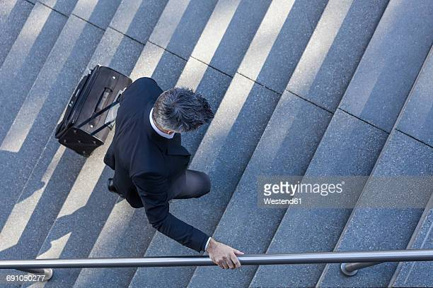 Businessman walking with suitcase on stairs