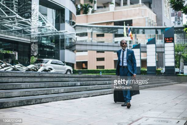 businessman walking with suitcase - ambassador stock pictures, royalty-free photos & images