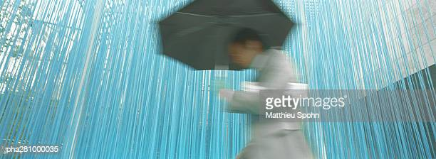 Businessman walking with umbrella, low angle view, panoramic