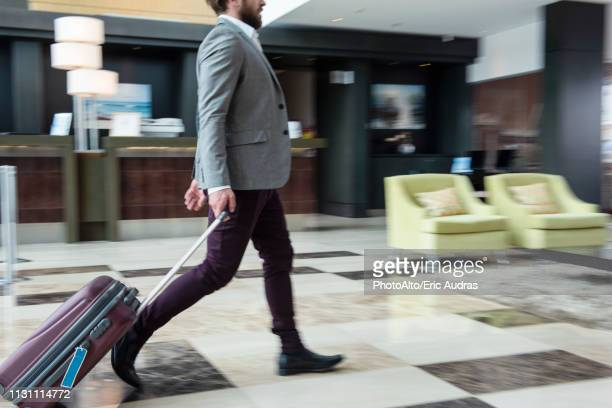 businessman walking with wheeled luggage - wheeled luggage stock photos and pictures