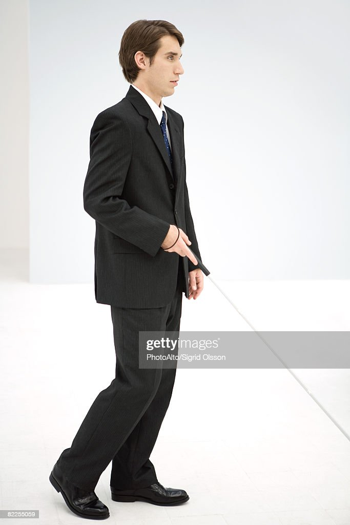 Businessman walking with white cane, side view : Stock Photo