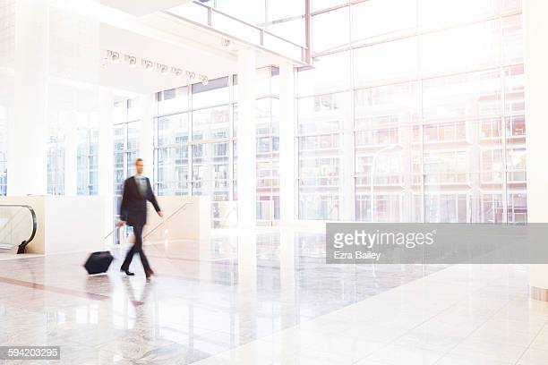 Businessman walks across large modern space.