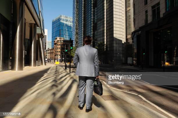 Businessman walks along a street in the City of London, U.K., on Monday, July 20, 2020. U.K. Prime Minister Boris Johnson nudged Britons back to...