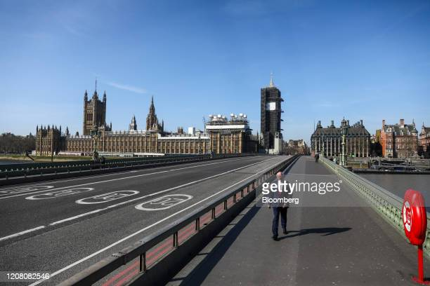 Businessman walks along a Westminster Bridge in view of the Houses of Parliament in London, U.K., on Tuesday, March 24, 2020. The U.K. Is in lockdown...
